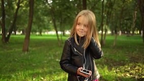 Girl in a leather jacket listening to music in park. Cute little blonde girl wearing a leather jacket listening to the music standing in a park on a summer day stock video footage
