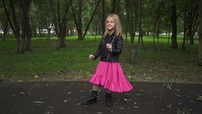 Girl in dress and jacket dancing in a park. Cute little blonde girl wearing a leather jacket and a pink dress is dancing while standing in a park on a summer day stock video