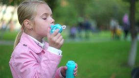 Cute little girl playing with soap bubbles outside stock video