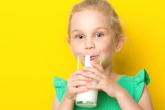 Cute kid drinking milk on blue background. Cute little blue-eyed girl is drinking milk from a glass beaker, on a yellow background stock photography