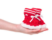 Cute little bootee. In the female hand isolated over white background Stock Photography