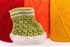 Cute little bootee. Over bright acrylic yarn background Stock Image