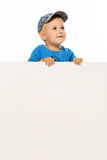 Cute little boy is above white blank poster looking up. White background Stock Photos