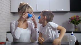 Joyful mom and son sticking handmade slime on face stock footage