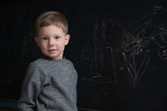 Cute little boy against dark blackboard Royalty Free Stock Photography