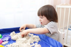 Cute little boy age of 2.11 years plays kinetic sand Stock Photos