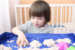 Cute little boy age of 2.11 years plays kinetic sand at home Royalty Free Stock Photo
