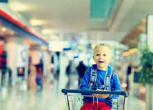 Cute little boy at airport riding on luggage cart Royalty Free Stock Photography
