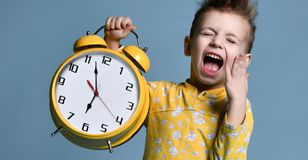 Cute little boy with alarm clock,isolated on blue. Funny kid pointing at alarm clock at 7 o`clock at morning. stock image