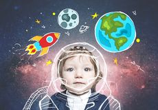 Cute little boy in astronaut suit in doodle space. Adorable little boy in suit dreaming of becoming astronaut. Open space background, rocket, Earth and Moon royalty free stock photography