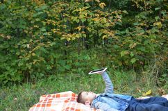 Cute little boy in an autumn park on a blanket. Reads plays a tablet. electronic wireless digital. stock images
