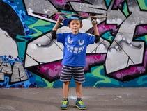 Cute little boy balancing a skateboard on his head Stock Photos