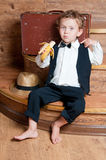 Cute little boy with a banana. Cute little boy with a banana in his hand sitting on the steps. Photo of retro style Stock Photography