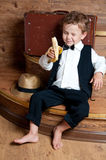 Cute little boy with a banana. Cute little boy with a banana in his hand sitting on the steps. Photo of retro style Royalty Free Stock Image