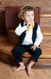 Cute little boy with a banana. Cute little boy with a banana in his hand sitting on the steps. Photo of retro style Stock Photo