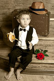 Cute little boy with a banana in his hand sitting. On the steps. Photo of retro style Royalty Free Stock Images