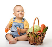 Cute little boy with basket full of vegetables. Cute little boy is sitting on the floor with basket full of vegetables, isolated over white Stock Photography