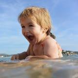 Cute little boy bathes in water. Stock Photo