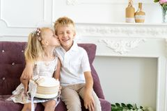 Sister brother birthday party. Cute little boy and beautiful girl are sitting on a chair together. Younger sister congratulates his older brother on his birthday royalty free stock photography