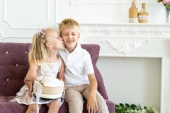 Sister brother birthday party. Cute little boy and beautiful girl are sitting on a chair together. Younger sister congratulates his older brother on his birthday royalty free stock photo