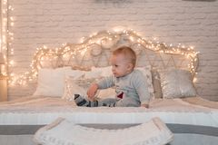 Cute little boy on bed. Cristmas lights background stock images