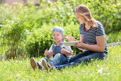 Cute little boy being fed outdoors on the grass Royalty Free Stock Photos