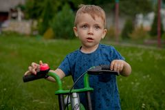 A cute little boy with a bicycle near the house, a sport for children, an active family on the street Stock Photo