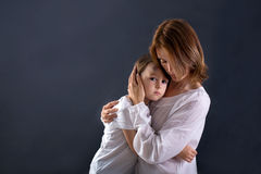 Cute little boy with big bump on his forehead from falling, hugg Royalty Free Stock Images