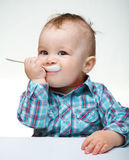 Cute little boy is biting spoon Royalty Free Stock Image
