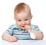 Cute little boy is biting spoon Royalty Free Stock Images