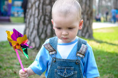 Cute little boy blowing on a pinwheel Royalty Free Stock Photos