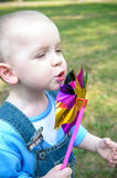 Cute little boy blowing on a pinwheel Stock Image