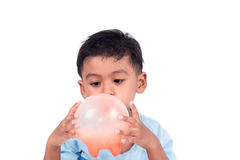 Cute little boy blowing red balloon royalty free stock photos