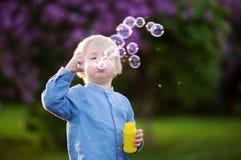 Cute little boy blowing soap bubbles in park Stock Images