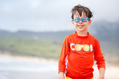 Cute little boy in blue swim goggles on beach Stock Photos