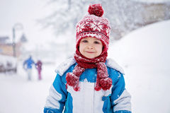 Cute little boy in blue winter suit, playing outdoor in the snow Stock Photo