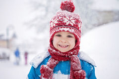 Cute little boy in blue winter suit, playing outdoor in the snow Stock Photography
