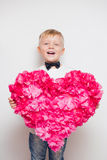 Cute little boy in bow tie holding big heart from paper flowers Stock Images