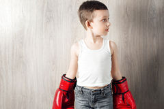 Cute little boy with boxing gloves large size. Portrait of a sporty child engaged in box. fooling around and not serious Royalty Free Stock Photography