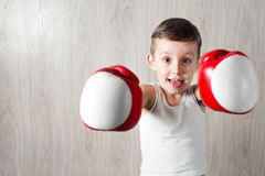 Cute little boy with boxing gloves large size. Portrait of a sporty child engaged in box. fooling around and not serious Stock Images