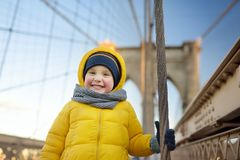 Cute little boy on Brooklyn Bridge with skyscrapers on background royalty free stock photos