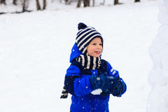 Cute little boy building snowman in winter Royalty Free Stock Photo