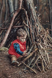 Cute little boy building a wooden shelter Stock Image