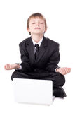 Cute little boy in business suit sitting in yoga pose with lapto Royalty Free Stock Images