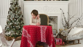 Cute little boy calling Santa while sitting on a big armchair at home over Chirstmas tree background stock video footage