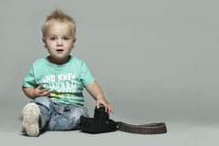 Cute little boy with camera. Grey big background Royalty Free Stock Photography