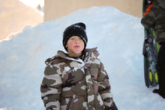 Cute little boy in camo ski jacket eating snow. Royalty Free Stock Photography
