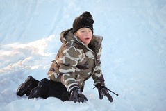 Cute little boy in camo ski jacket playing in snow. Royalty Free Stock Photos