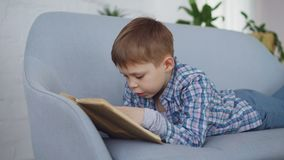 Cute little boy in casual clothes is reading funny book aloud lying on comfortable sofa and laughing. Happy childhood. Cute little boy in casual clothes is stock footage