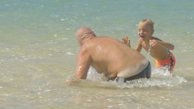 Cute boy catches funny daddy playing in calm ocean water